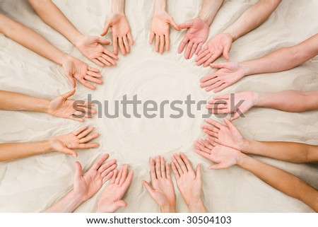 Image of several friends? hands on sand in the form of circle - stock photo
