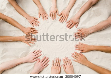 Image of several hands on sand in the form of circle - stock photo