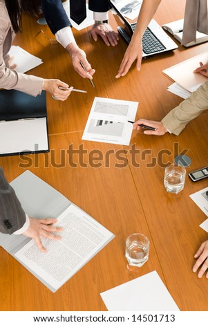 Image of several hands pointing at document at business conference - stock photo