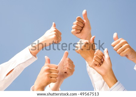 Image of several human hands showing thumbs up against clear blue sky - stock photo