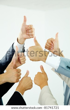 Image of several human hands showing thumbs up in isolation - stock photo