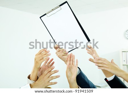 Image of several human hands trying to get paper from male hand - stock photo