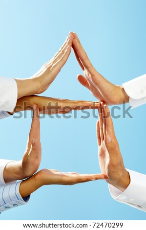 Image of several human palms forming house structure against clear blue sky - stock photo