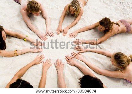 Image of several teens lying on beach and keeping their hands on sand in the form of circle - stock photo