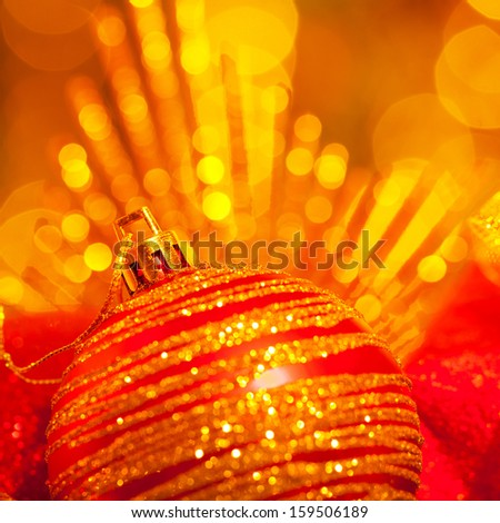Image of shiny Christmas tree decoration, beautiful red bubble on glowing yellow lights background, New Year greeting card, happy holiday concept, festive garland glitters, x-mas ornament still life  - stock photo