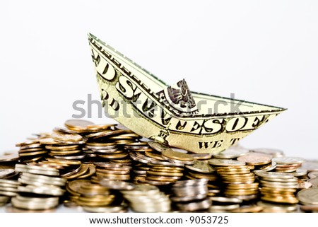 Image of ship made of dollar above a lot of coins - stock photo