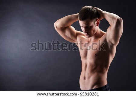 Image of shirtless man in jeans looking downwards with his hands on top of head - stock photo