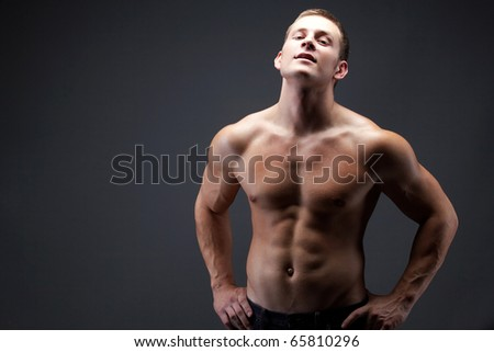 Image of shirtless man in jeans posing in front of camera