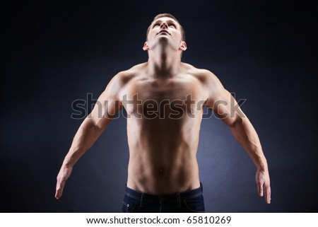 Image of shirtless man looking upwards in front of camera - stock photo