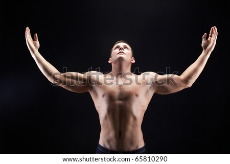 Image of shirtless man looking upwards with raised arms on black background