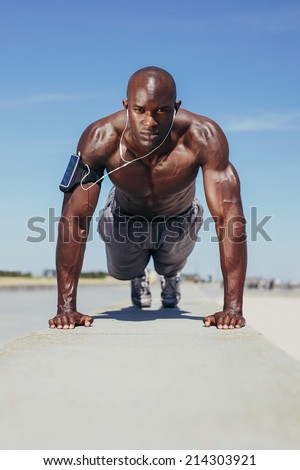Image of shirtless young man doing push-ups. Muscular young fitness model exercising. African male model workout outdoors. - stock photo