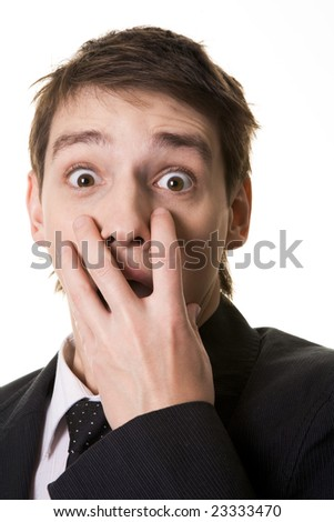 Image of shocked businessman hiding his mouth under hand and looking at camera with widened eyes - stock photo