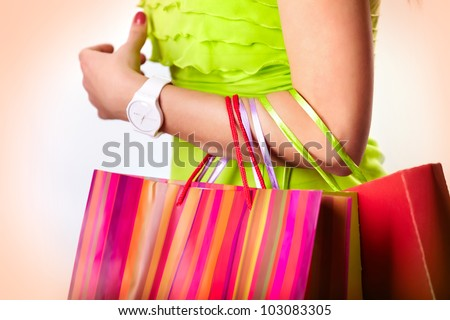 Image of shopaholic arm with three shopping bags - stock photo