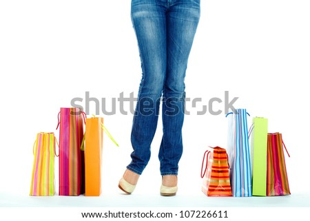 Image of shopaholic legs and shopping bags near by - stock photo