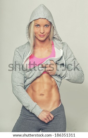 Image of shy blondie in sportswear who is demonstrating her abs - stock photo