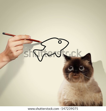 Image of siamese cat catching drawed fish - stock photo