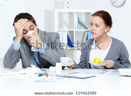 Image of sick businessman and his secretary giving him a cup of tea and lemon in office - stock photo