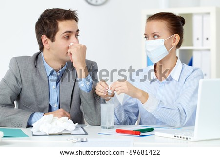 Image of sick businessman with tissue looking at his colleague in mask dissolving solution for him in office