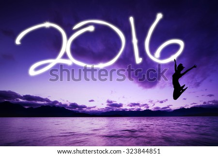 Image of silhouette girl dancing at the shore while celebrating new year and drawing numbers 2016 on the air