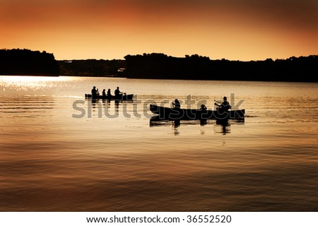 Image of silhouette of canoers on a lake - stock photo