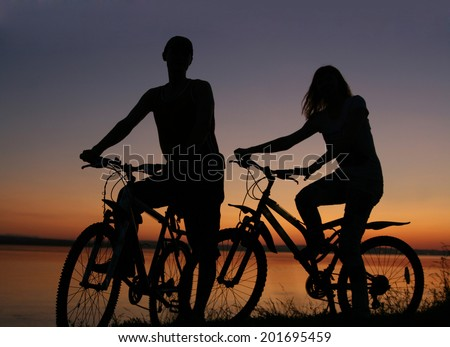 Image of silhouette sporty couple on bicycles outdoors against water in sea texture blue and yellow sunset sky. Copy space for inscription Reflection on the ocean - stock photo
