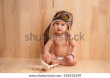 Image of Six months old East Asian baby boy sitting on wooden background with wooden air plane, sweet little baby dreaming of being pilot - stock photo