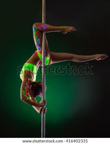 Image of slender girl hanging upside down on pylon - stock photo