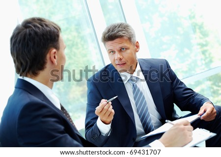 Image of smart boss explaining to colleague business idea