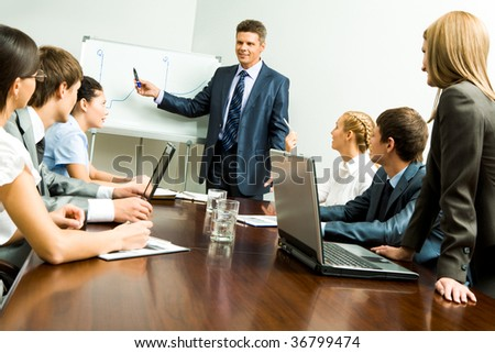Image of smart business people listening to confident man while he explaining something on whiteboard during seminar - stock photo