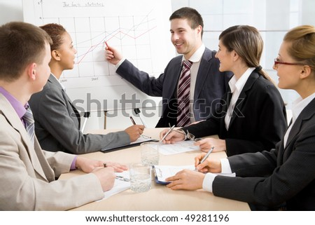 Image of smart business people looking at their leader while he explaining something on whiteboard during seminar - stock photo