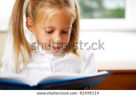 Image of smart child reading interesting book in classroom. Horizontal Shot. She is involved and thinking - stock photo