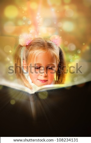Image of smart child reading interesting book in classroom. Vertical Shot. She is involved and attentive
