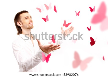 Image of smart guy with open palms looking at pink paper butterflies - stock photo