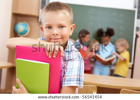Image of smart schoolboy looking at camera with smile on background of classmates