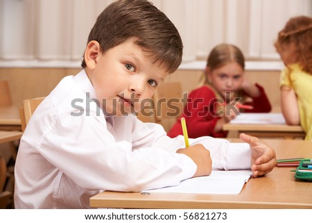 Image of smart schoolboy sitting at desk and drawing while looking at camera during lesson