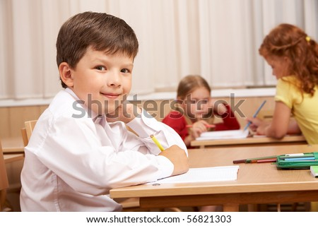 Image of smart schoolboy sitting at desk and looking at camera during lesson - stock photo