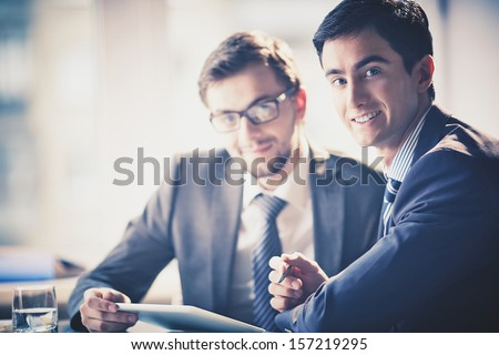 Image of smart young businessmen looking at camera at meeting - stock photo
