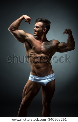Image of smiling bodybuilder admires his biceps - stock photo