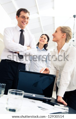 Image of smiling boss looking at business lady presenting computer work in the office