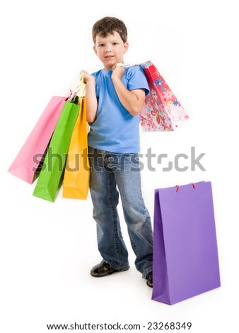Image of smiling boy holding bags with presents or shoppings looking at camera - stock photo