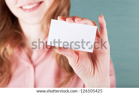 Image of smiling business woman holding her visiting card - stock photo