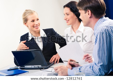 Image of smiling businesswoman pointing at laptop monitor while two colleagues looking at her