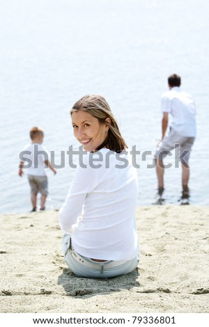 Image of smiling female sitting on sandy shore and looking at camera - stock photo