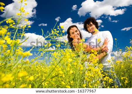 Image of smiling guy embracing his girlfriend while both looking at camera among yellow flowers - stock photo