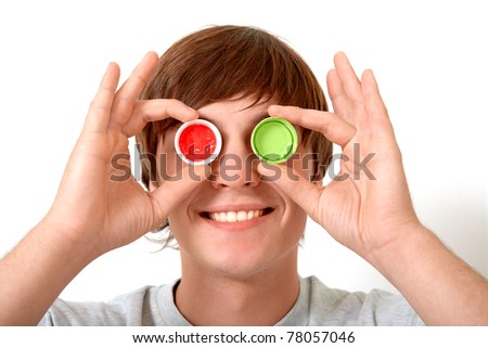 Image of smiling guy hiding eyes behind plastic corks with green and red paint