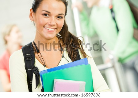 Image of smiling student holding books and looking at camera - stock photo
