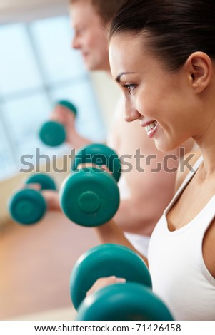 Image of smiling woman and guy doing lifting exercise with barbells in hands - stock photo
