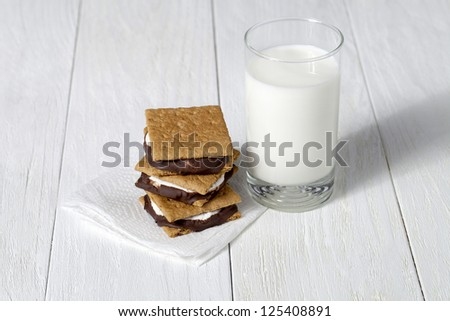 Image of smores sandwich with glass of milk on the wooden table - stock photo