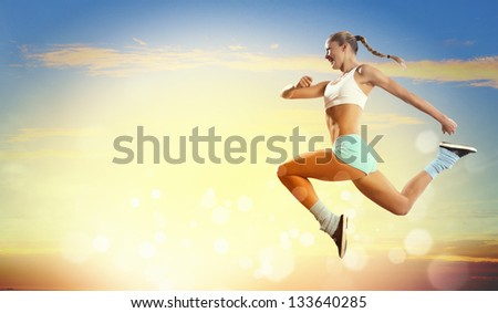 Image of sport girl in jump against cloudy background - stock photo