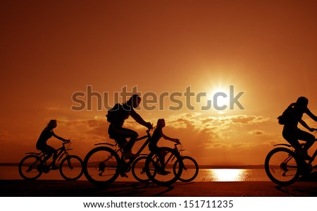 Image of sporty company four friends on bicycles outdoors against sunset. Silhouette A lot phases of motion of a single cyclist along the shoreline coast Reflection on water Space for inscription